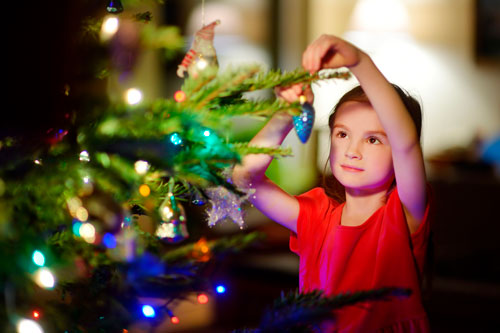 girl putting an ornament on a christmas tree