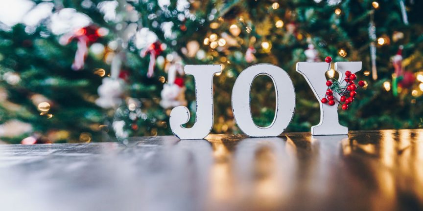 Joy letters in front of a Christmas tree