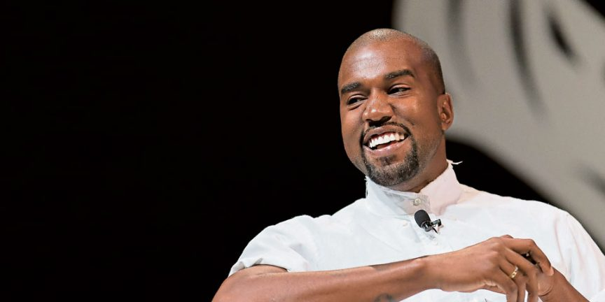 kanye west smiling whilst wearing a tie mic