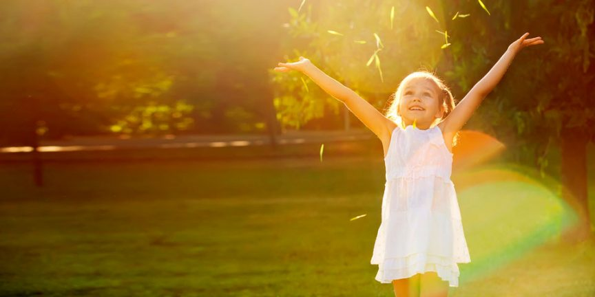 little girl standing in a green field with her arms in the air after throwing grass
