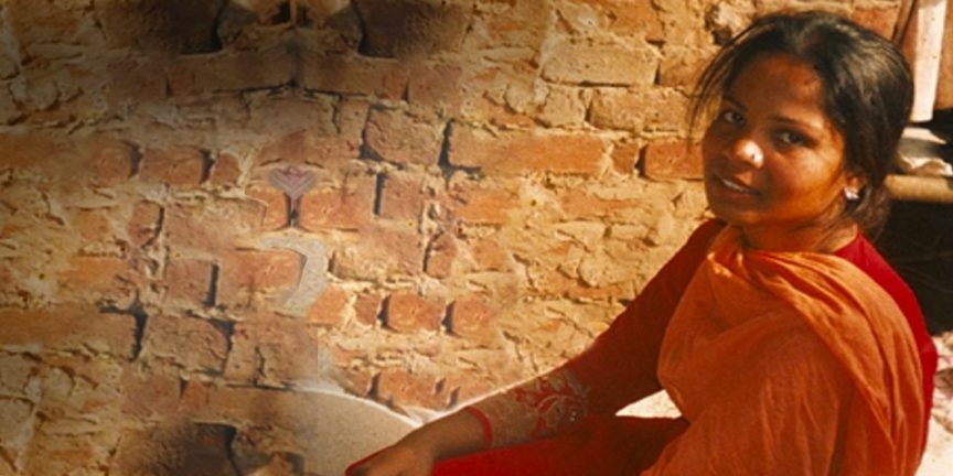 Asia Bibi sat in a small room with brick walls, smiling at the camera