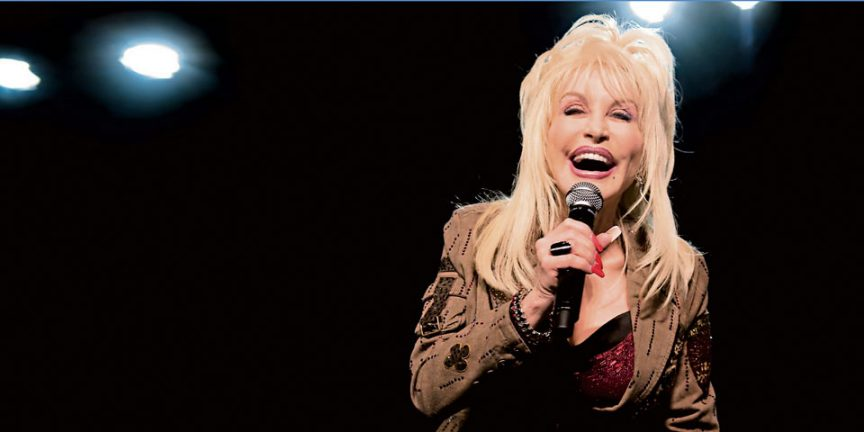 Dolly Parton singing into a microphone on a black backdrop
