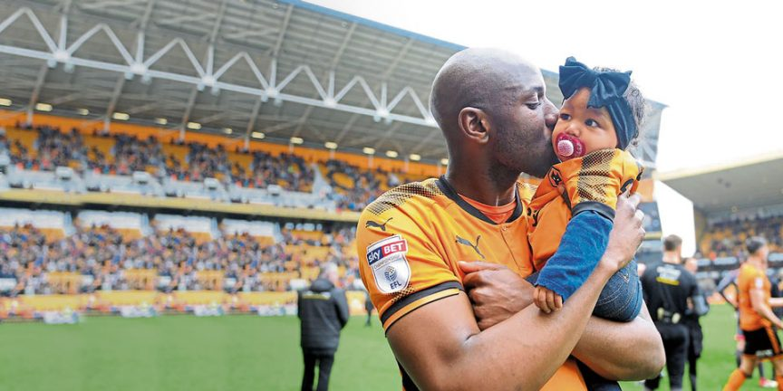 Benik Afobe holding his daughter while standing on a football pitch