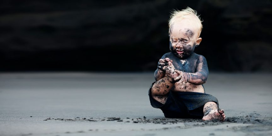 a child sitting on the ground covered in mud
