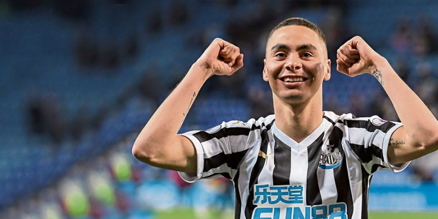 Miguel Almiron celebrating with both arms in the air on a football pitch