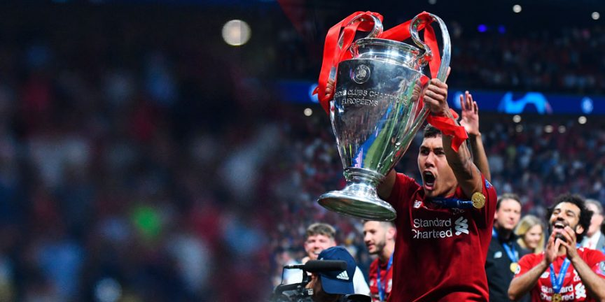 Roberto Firmino holding the Champions League trophy aloft after winning the competition in 2019