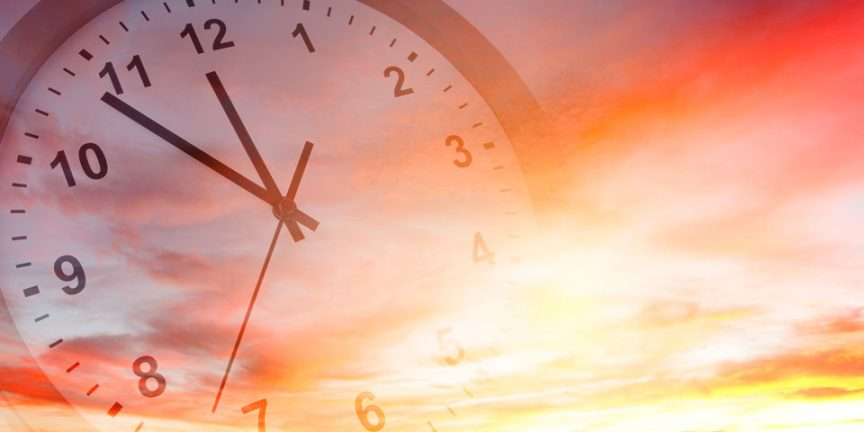 a faded clock set against a picturesque sunset
