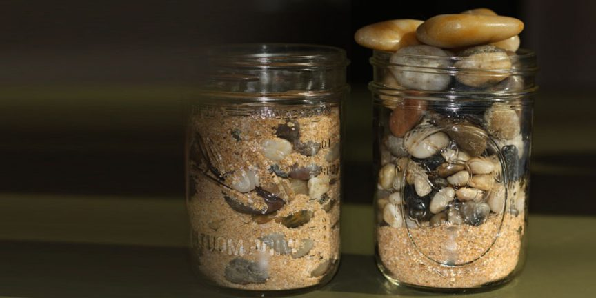 two glass jars side by side, filled with sand, pebbles and rocks