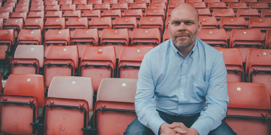 Simon Edwards sitting on a seat in an empty football stadium