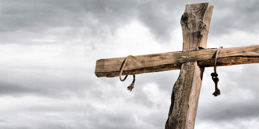 an empty cross pictured against a clouded grey sky