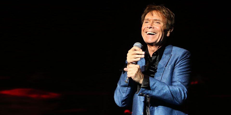 Cliff Richard holding a mic on stage against a black background